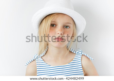 Image of beautiful 5-year female kid wearing stylish clothes looking with serious expression at the camera. Lifestyle and people concept. Adorable Caucasian little girl with green eyes and blonde hair - stock photo