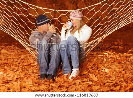 Image of beautiful young couple sitting in hammock and drink hot chocolate - stock photo