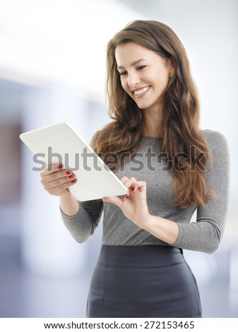 Image of beautiful young woman standing while holding digital tablet in her hands and reading text. Businesswoman working at office.