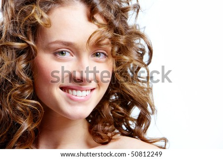 Image of beautiful young woman with curly hairs looking at camera - stock photo