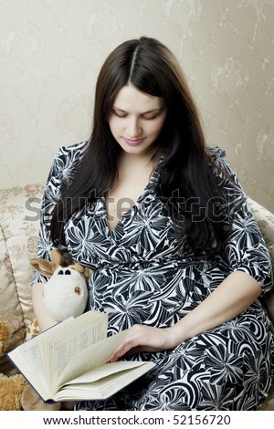 Image of beauty pregnant woman who reads book sitting on the sofa - stock photo
