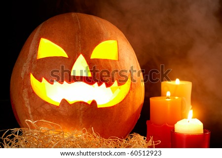 Image of big pumpkin with burning candle inside and three candles near by - stock photo