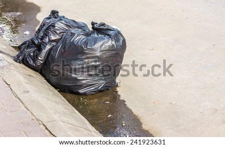 image of black garbage bag on the roadside. - stock photo