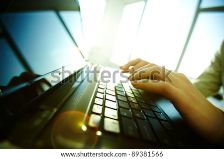 Image of black laptop keyboard with female hands over it