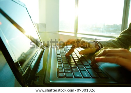 Image of black laptop keyboard with female hands touching it - stock photo