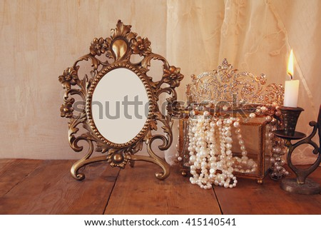 image of blank vintage frame, pearls and burning candle on wooden table. vintage filtered  - stock photo