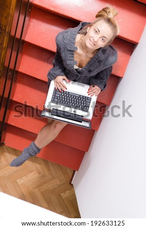 image of blond young pretty businesswoman or female student having fun working typing on laptop computer relaxing sitting on stairs at home happy smiling & looking up at camera portrait  - stock photo