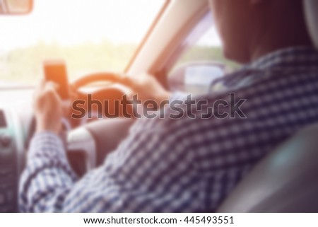 image of blur Concept of dangerousman used cell phone while driving are dangerous for other people,blur image,transportation and vehicle concept - man using phone while driving the car - stock photo
