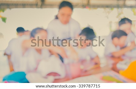image of blur kid and mom drawing and painting with mom on table in bright sunny playroom for background usage . (vintage tone)