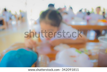image of blur kid drawing and painting on table in bright sunny playroom for background usage .