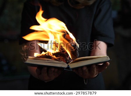 Image of book burning in woman hands in dark forest - stock photo