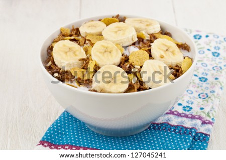 Image of bowl of cereal with banana with table cloth wooden table