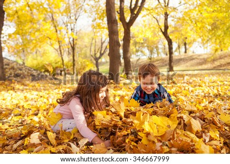 Image of boy and girl playing with autumn leaves in the park, shallow depth of field