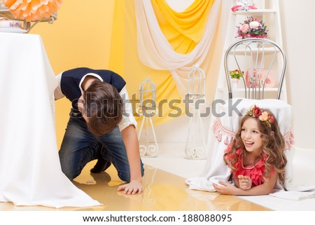 Image of brother and sister play hide-and-seek - stock photo