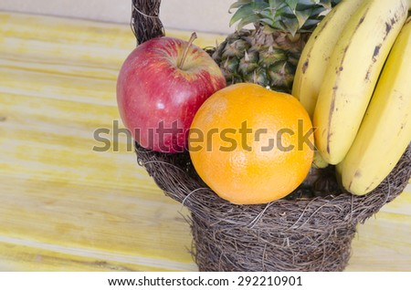 Image of brown basket with fruits on wooden table. - stock photo