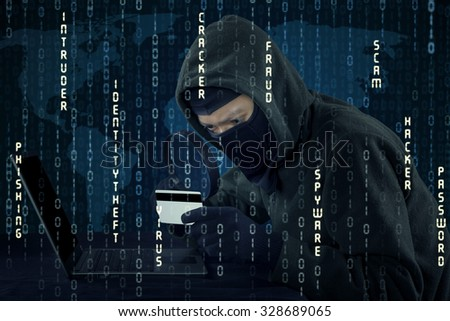 Image of burglar wearing mask and stealing credit card information with laptop computer - stock photo