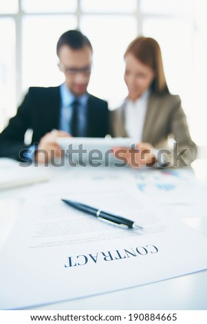 Image of business contract on workplace with two colleagues using touchpad on background - stock photo