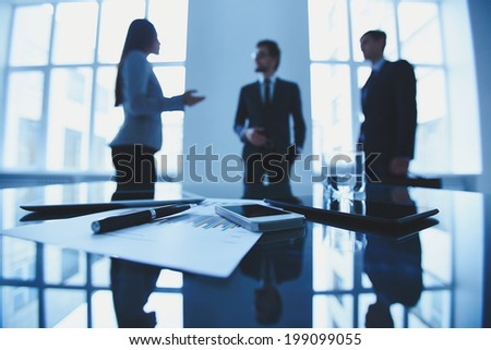 Image of business document and electronic devices at workplace with group of business people talking on background - stock photo