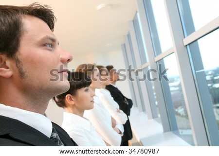 Image of business group standing in line and looking through window with handsome leader in focus