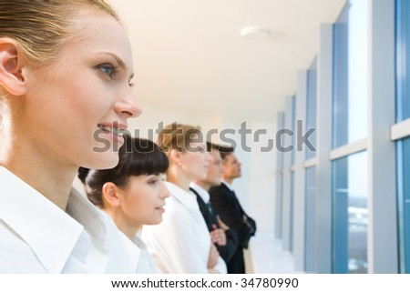 Image of business group standing in line and looking through window with pretty female in front