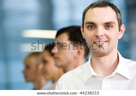Image of business group standing in line with handsome leader in front - stock photo