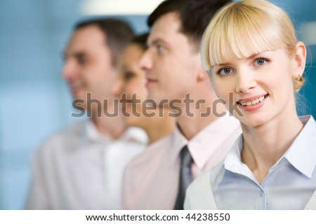 Image of business group standing in line with pretty female in front - stock photo