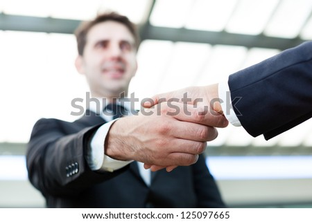 Image of business handshake at the office - stock photo
