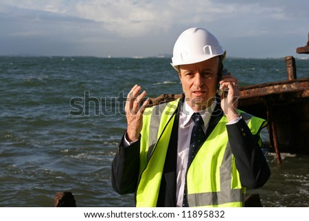 Image of business man at a ship wreck, talking on the phone - stock photo