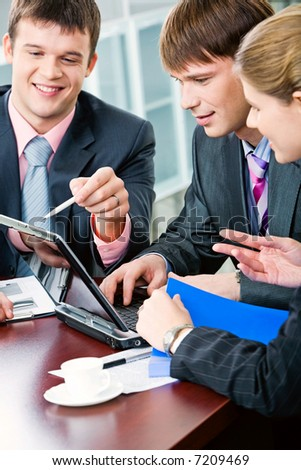 Image of business man holding pen and explaining the correct way of business plan to his colleagues - stock photo