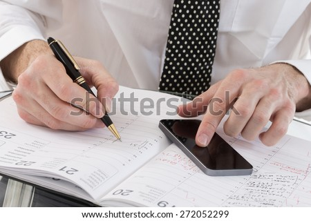 Image of  business man' s hands planning on agenda book, and smart phone  in office - stock photo