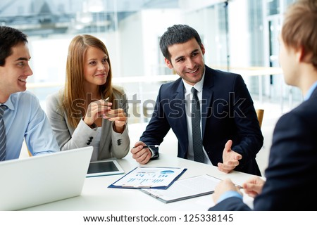 Image of business partners discussing documents and ideas at meeting - stock photo