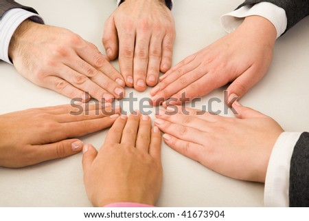 Image of business partners hands making circle on table