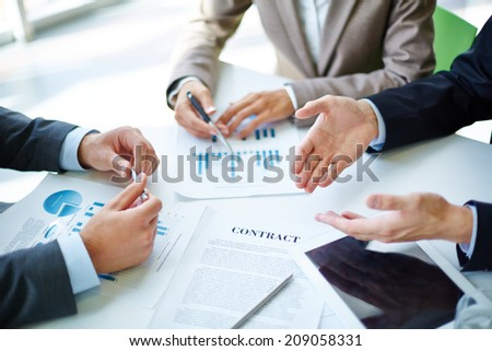 Image of business partners hands over business objects on workplace at meeting - stock photo