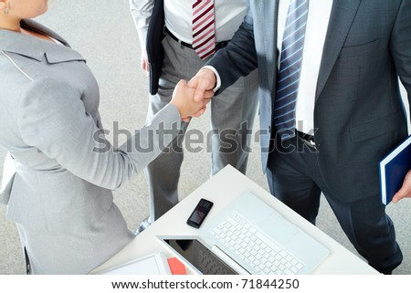 Image of business partners handshaking after signing contract - stock photo
