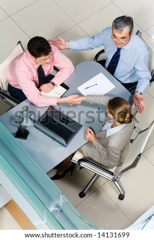 Image of business partners handshaking at meeting while friendly man sitting near by - stock photo