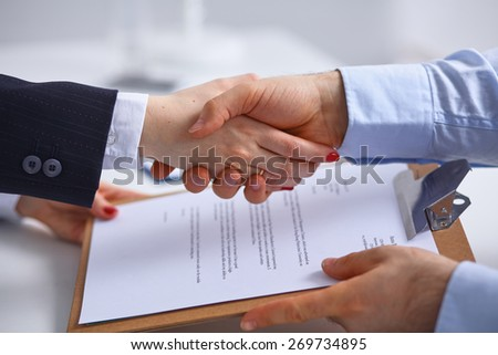 Image of business partners handshaking over business objects - stock photo