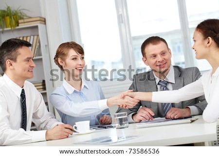 Image of business partners making an agreement with two men near by - stock photo