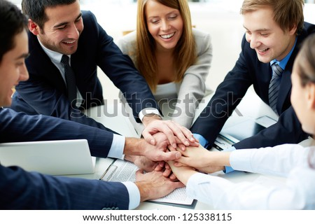 Image of business partners making pile of hands at meeting - stock photo