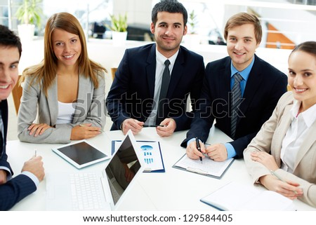 Image of business partners sitting at workplace and looking at camera - stock photo