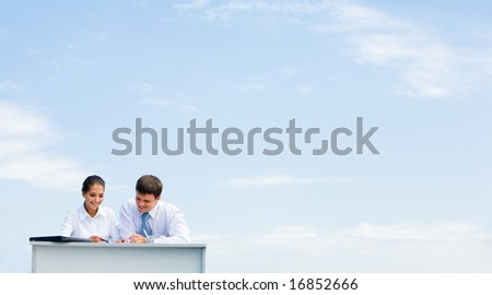 Image of business partners sitting in low left corner and communicating on background of azure sky - stock photo
