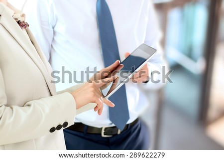 Image of business partners using digital tablet at meeting - stock photo