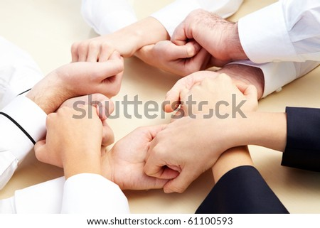 Image of business people hands holding other symbolizing support and power