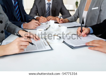 Image of business people hands with ballpoints writing on papers while planning work - stock photo