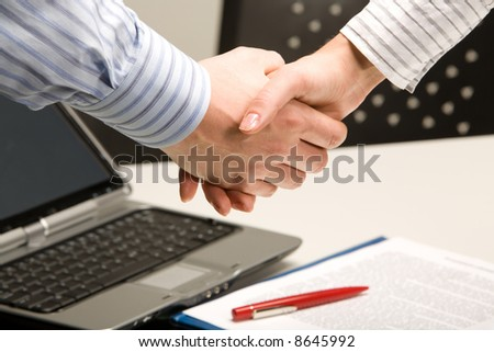 Image of business people shaking hands in a working environment