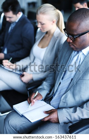 Image of business people sitting in rows and making notes at conference - stock photo
