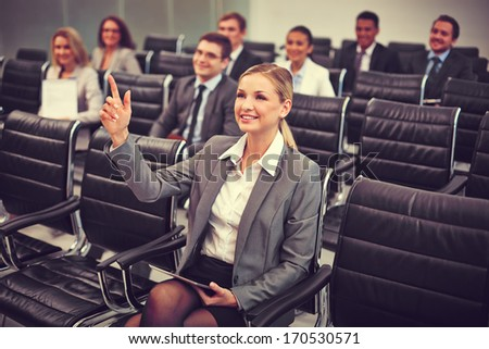 Image of business people sitting in rows at seminar with pretty woman in front raising her arm - stock photo