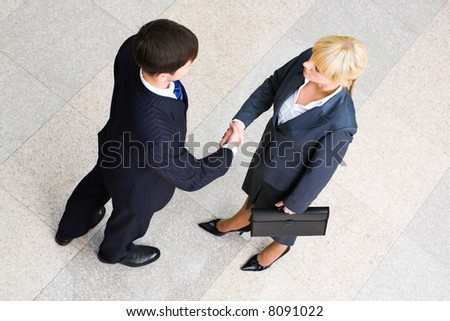 Image of business people standing and shaking hands in the room - stock photo