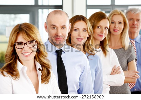 Image of business people standing at office in a row. Portrait of mixed age businesswomen and businessmen standing with arms crossed and looking at camera. - stock photo