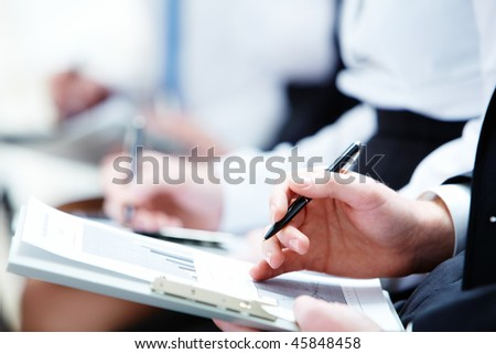 Image of business person hands with documents making notes at the lecture