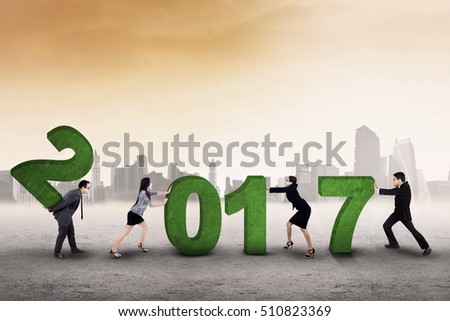 Image of business team trying to arrange number 2017, symbolizing of working together for the future